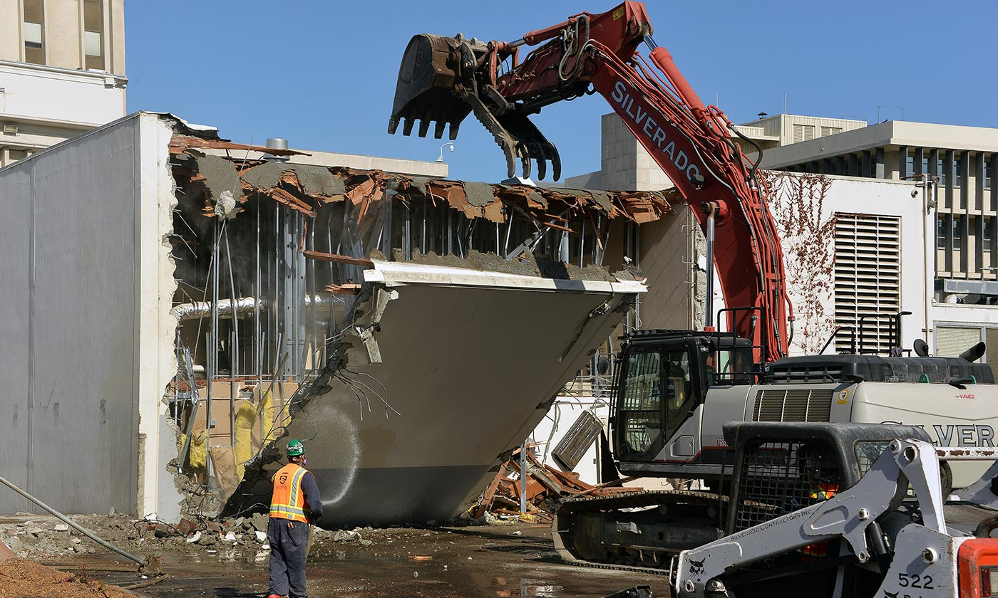 Construction crew demolishing building with tractor